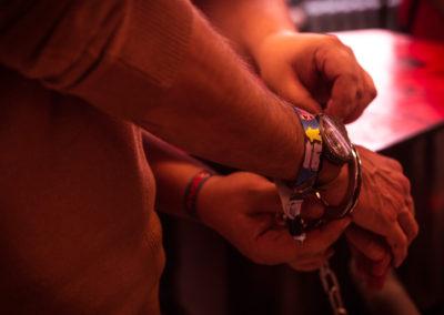 """Photographie d'une personne menottée lors d'une partie de jeu de l énigme éphémère """"mal barré"""" de fug game live escape Besançon"""